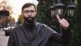 Πορτρέτο του νέου ελκυστικού γενειοφόρου ατόμου στα γυαλιά και της εξέτασης τη κάμερα Το άτομο με την παραγωγή προσώπου πόκερ φυλ απόθεμα βίντεο
