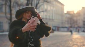 Πορτρέτο του νέου ελκυστικού θηλυκού στη μοντέρνη εξάρτηση που κάνει ένα selfie απόθεμα βίντεο