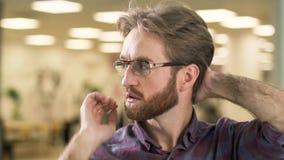 Πορτρέτο του νέου ελκυστικού σοβαρού γενειοφόρου τύπου στα γυαλιά και το περιστασιακό πουκάμισο καρό που ανησυχούν με ένα δύσκολο απόθεμα βίντεο