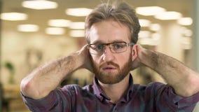 Πορτρέτο του νέου ελκυστικού σοβαρού γενειοφόρου τύπου στα γυαλιά που ανησυχούν με ένα δύσκολο πρόβλημα φιλμ μικρού μήκους