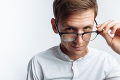Πορτρέτο του νέου ελκυστικού τύπου στα γυαλιά, στο άσπρο πουκάμισο, που απομονώνεται στο άσπρο υπόβαθρο, για τη διαφήμιση, την ει στοκ φωτογραφία με δικαίωμα ελεύθερης χρήσης