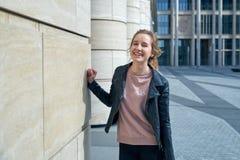 Πορτρέτο του νέου ελκυστικού χαμογελώντας ευτυχούς κοριτσιού σε ένα σακάκι δέρματος και των τζιν ενάντια στο σκηνικό της σύγχρονη στοκ εικόνα με δικαίωμα ελεύθερης χρήσης