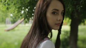 Πορτρέτο του νέου ελκυστικού brunette στο ουκρανικό φόρεμα κεντητικής που περπατά κατά μήκος του πάρκου φιλμ μικρού μήκους