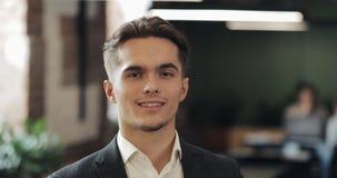 Πορτρέτο του νέου επιτυχούς επιχειρηματία στο πολυάσχολο γραφείο Όμορφος άνδρας υπάλληλος που εξετάζει τη κάμερα και το χαμόγελο  απόθεμα βίντεο