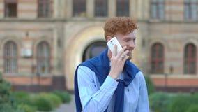 Πορτρέτο του νέου ευτυχούς ατόμου με την κόκκινη σγουρή τρίχα και της γενειάδας που χαμογελά και που μιλά μέσω του κινητού τηλεφώ απόθεμα βίντεο