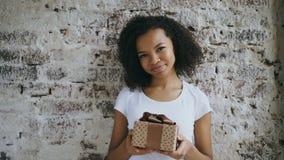 Πορτρέτο του νέου ευτυχούς αφρικανικού κιβωτίου και του χαμόγελου δώρων εκμετάλλευσης κοριτσιών στη κάμερα απόθεμα βίντεο