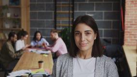 Πορτρέτο του νέου εύθυμου θηλυκού επιχειρηματία που εξετάζει τη κάμερα και που χαμογελά στο πολυάσχολο υπόβαθρο γραφείων ξεκινήμα φιλμ μικρού μήκους