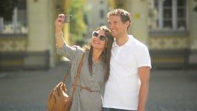 Πορτρέτο του νέου ζεύγους που παίρνει Selfie χρησιμοποιώντας Smartphone που στέκεται υπαίθρια στο τετράγωνο πόλεων κατά τη διάρκε φιλμ μικρού μήκους