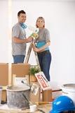 Πορτρέτο του νέου ζεύγους που χρωματίζει το σπίτι τους Στοκ Φωτογραφίες