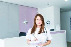 Πορτρέτο του νέου θηλυκού γιατρού με το βιβλίο σημειώσεων που εξετάζει τη κάμερα και που χαμογελά χαρωπά θέτοντας στην αίθουσα re στοκ φωτογραφία