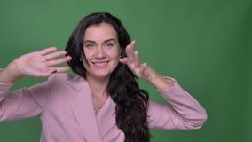 Πορτρέτο του νέου θηλυκού brunette vloger στο ρόδινο σακάκι που χορεύει με ικανοποίηση στη κάμερα στο πράσινο υπόβαθρο απόθεμα βίντεο
