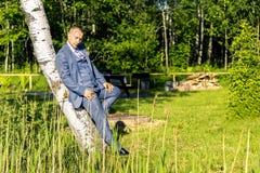Πορτρέτο του νέου και ελκυστικού ατόμου στο γκρίζο μπλε κοστούμι Στοκ Εικόνες
