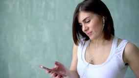Πορτρέτο του νέου κατάλληλου κοριτσιού που ακούει τη μουσική στα ακουστικά της στη γυμναστική απόθεμα βίντεο