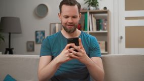 Πορτρέτο του νέου καυκάσιου ατόμου που χρησιμοποιεί τη σύγχρονη κινητή συνεδρίαση smartphone σε έναν καναπέ στο σπίτι, κινητό τηλ απόθεμα βίντεο