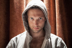 Πορτρέτο του νέου καυκάσιου ατόμου στην κουκούλα με την κόκκινη ΤΣΕ κουρτινών Στοκ Εικόνα