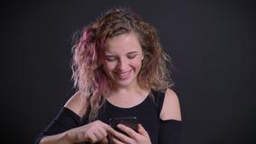 Πορτρέτο του νέου καυκάσιου κοριτσιού με τη ρόδινη προσοχή τρίχας στο smartphone της που γελά και που χαμογελά στο μαύρο υπόβαθρο απόθεμα βίντεο