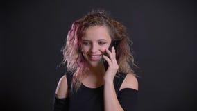 Πορτρέτο του νέου καυκάσιου κοριτσιού με τη ρόδινη τρίχα που μιλά ευτυχώς στο κινητό τηλέφωνο στο μαύρο υπόβαθρο φιλμ μικρού μήκους