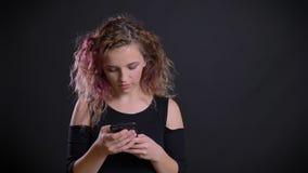 Πορτρέτο του νέου καυκάσιου κοριτσιού με τη ρόδινη τρίχα που προσέχει προσεκτικά στο smartphone της στο μαύρο υπόβαθρο φιλμ μικρού μήκους