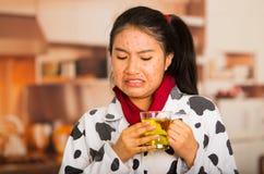 Πορτρέτο του νέου κοριτσιού με το πρόβλημα δερμάτων που πίνει κάποιο τσάι που κάνει τα ανόητα πρόσωπα Στοκ Εικόνα