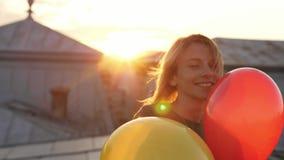 Πορτρέτο του νέου κοριτσιού που περπατά στην εκμετάλλευση καμερών στα χέρια μερικά μπαλόνια φιλμ μικρού μήκους