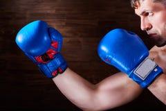 Πορτρέτο του νέου μαχητή μπόξερ με τα εγκιβωτίζοντας γάντια ενάντια στον ξύλινο τοίχο Στοκ Εικόνα