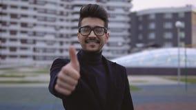 Πορτρέτο του νέου μοντέρνου επιχειρηματία στα γυαλιά και της εξέτασης τη κάμερα Το άτομο που χαμογελά και που κάνει φυλλομετρεί ε φιλμ μικρού μήκους
