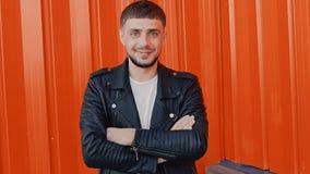 Πορτρέτο του νέου μοντέρνου θετικού ατόμου που στέκεται κοντά στο πορτοκαλί υπόβαθρο τοίχων φιλμ μικρού μήκους