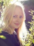 Πορτρέτο του νέου ξανθού κοριτσιού μεταξύ των κλάδων Στοκ Εικόνα