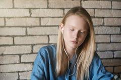 Πορτρέτο του νέου ξανθού κοριτσιού με τα ακουστικά στοκ φωτογραφία