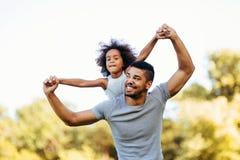 Πορτρέτο του νέου πατέρα που φέρνει την κόρη του στην πλάτη του Στοκ φωτογραφία με δικαίωμα ελεύθερης χρήσης