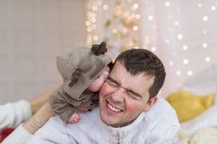 Πορτρέτο του νέου πατέρα στα άσπρα ενδύματα που κρατούν το νεογέννητο μωρό τους στα πλαίσια των διακοσμήσεων Χριστουγέννων Στοκ Φωτογραφίες