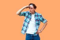 Πορτρέτο του νέου προσεκτικού σοβαρού ατόμου περιστασιακό μπλε ελεγμένο headband πουκάμισων που στέκεται με το χέρι στο μέτωπο κα στοκ φωτογραφία