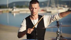 Πορτρέτο του νέου τυμπανιστή που εκπαιδεύει το παιχνίδι ενός μουσικού οργάνου στην ημέρα φιλμ μικρού μήκους