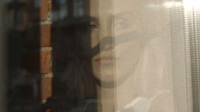 Πορτρέτο του νέου λυπημένου κοιτάγματος γυναικών μέσω του παραθύρου απόθεμα βίντεο