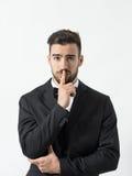Πορτρέτο του νέου φοβησμένου ατόμου με το δάχτυλο πέρα από τα χείλια του που εξετάζει τη κάμερα Στοκ φωτογραφίες με δικαίωμα ελεύθερης χρήσης