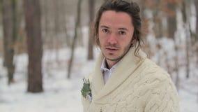 Πορτρέτο του νέου χαμογελώντας ατόμου στο χειμερινό δάσος φιλμ μικρού μήκους