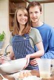 Πορτρέτο του νέου ψησίματος ζεύγους στην κουζίνα από κοινού Στοκ εικόνα με δικαίωμα ελεύθερης χρήσης