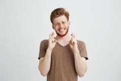 Πορτρέτο του νέου όμορφου ατόμου με την επίκληση γενειάδων που ελπίζει πέρα από το άσπρο υπόβαθρο Στοκ Εικόνες