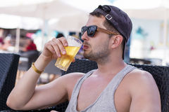 Πορτρέτο του νέου όμορφου ατόμου που πίνει την κρύα αναζωογονώντας μπύρα Στοκ Φωτογραφία