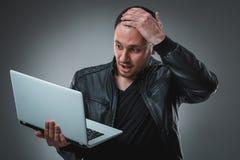 Πορτρέτο του νέου όμορφου ατόμου που χρησιμοποιεί το lap-top, που φορά το μαύρο σακάκι δέρματος Στοκ φωτογραφία με δικαίωμα ελεύθερης χρήσης