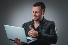 Πορτρέτο του νέου όμορφου ατόμου που χρησιμοποιεί το lap-top, που φορά το μαύρο σακάκι δέρματος Στοκ Φωτογραφίες