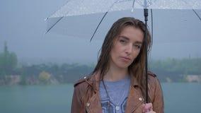 Πορτρέτο του νέου όμορφου κοριτσιού κάτω από μια ομπρέλα σε βροχερό απόθεμα βίντεο