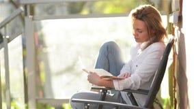 Πορτρέτο του νέου όμορφου κοριτσιού με την καυκάσια διαβασμένη εμφάνιση ενδιαφέρουσα συνεδρίαση βιβλίων σε ένα μπαλκόνι Η γυναίκα φιλμ μικρού μήκους