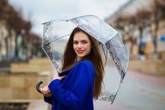 Πορτρέτο του νέου όμορφου κρυψίματος κοριτσιών κάτω από μια ομπρέλα Στοκ Φωτογραφίες