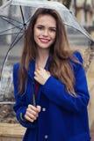 Πορτρέτο του νέου όμορφου κρυψίματος κοριτσιών κάτω από μια ομπρέλα Στοκ Εικόνες