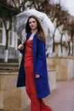 Πορτρέτο του νέου όμορφου κρυψίματος κοριτσιών κάτω από μια ομπρέλα Στοκ Φωτογραφία