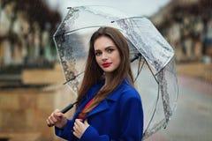Πορτρέτο του νέου όμορφου κρυψίματος κοριτσιών κάτω από μια ομπρέλα Στοκ εικόνες με δικαίωμα ελεύθερης χρήσης