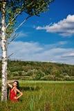 Πορτρέτο του νέου όμορφου κόκκινου φωτεινού φορέματος γυναικών brunette Στοκ Φωτογραφίες