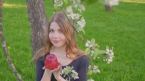 Πορτρέτο του νέου όμορφου μήλου εκμετάλλευσης γυναικών προσώπου θερινή φύση υποβάθρου δέντρων μηλιάς άνοιξης στην ανθίζοντας Άνοι απόθεμα βίντεο