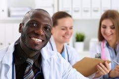 Πορτρέτο του νέου όμορφου μαύρου αρσενικού γιατρού με τους συναδέλφους Στοκ Εικόνες
